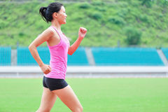 Asian woman runner running. In sports ground outdoor Stock Images
