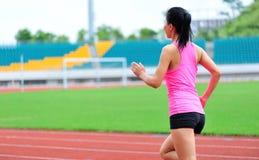 Asian woman runner running. In sports ground outdoor Stock Photos
