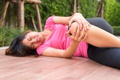 Asian woman runner touching her injured knee at outdoor - pain c Royalty Free Stock Photography
