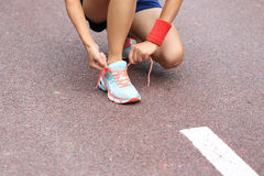 Asian woman runner tying shoelace Stock Images