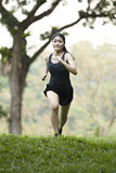 Asian woman running cross country. Royalty Free Stock Photography
