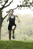 Asian woman running cross country. Royalty Free Stock Photos
