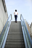 Asian  woman running on escalator stairs Stock Images