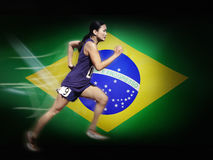 Asian woman running in front of Brazilian Flag Stock Photography