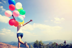 Asian woman running on mountain peak rock with colored balloons Royalty Free Stock Photography