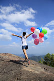 Asian woman running on mountain peak rock with colored balloons Stock Image