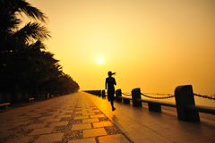 Asian woman running seaside morning Stock Photo