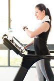 Asian woman running treadmill use smartwatch check pulse rate Royalty Free Stock Photography