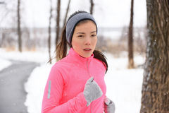Asian woman running in winter gloves and headband royalty free stock photo