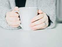 Asian woman 30s to 40s hand with cloth hold the white hot coff. Ee cup from hand warming and drink on morning time with soft focus background Royalty Free Stock Photography