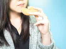 Asian woman 30s to 40s hand with cloth hold and eat donut on m Stock Photos