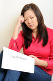 Asian woman sad over Lay-Of notice. Attractive Asian woman seated and looking depressed over a lay-off notice that she is holding Stock Images