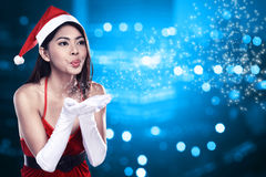 Asian woman in santa claus costume blowing magic dust Royalty Free Stock Images