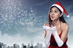 Asian woman in santa claus costume blowing magic dust Royalty Free Stock Photos