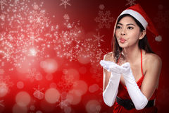 Asian woman in santa claus costume blowing magic dust Stock Images