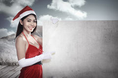 Asian woman in santa claus costume holding blank banner Royalty Free Stock Photography
