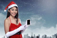 Asian woman in santa claus costume holding cellphone Stock Photo