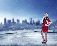 Asian woman in santa claus costume. Standing on building rooftop Royalty Free Stock Photo
