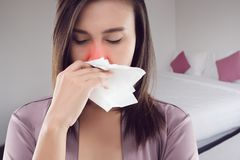 Dust Allergies Symptoms. Asian woman in satin nightwear feeling unwell and sneeze at bedroom, Dust allergies symptoms, People caught cold and allergy royalty free stock photo