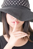Asian woman saying hush be quiet. Close-up portrait of asian woman saying hush be quiet. Half covered face by black hat. Isolated on the white background Stock Image