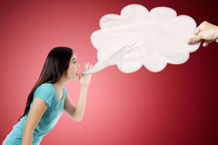 Asian woman saying something. Photo of Asian woman saying something to an empty cloud, shot with red background Royalty Free Stock Photo