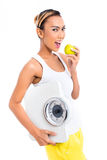 Asian woman with scale eating healthy. Young Asian woman losing weight by living healthy and eating fruits Stock Photos