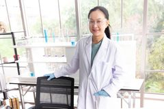 Asian woman scientist wearing glasses stand in laboratory room royalty free stock photos