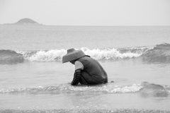 Asian Woman searching clam in the beach Royalty Free Stock Photo