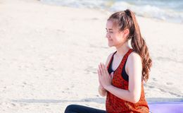 Asian woman seated doing Hand Mudra yoga pose on sand at coastli Stock Images