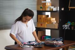 Free Asian Woman Seller Are Measuring Trouser Sizes According To Their Customers` Orders Through Online Shopping Royalty Free Stock Photo - 193258685