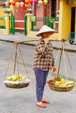 Asian woman seller carrying Rambutan mango and banana Royalty Free Stock Images