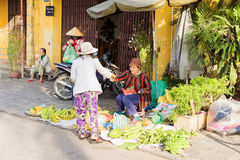Asian woman selling bunches of bananas in the street market Stock Photography