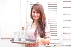 Asian woman serving a glass of water Stock Photo