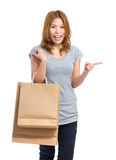 Asian woman with shopping bag and finger pointing aside Stock Images