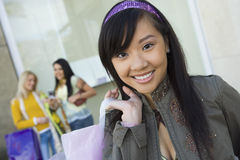 Asian Woman With Shopping Bag And Friends In Background Royalty Free Stock Photography