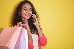 Asian woman with shopping bag talking on a mobile phone. Close up portrait of asian woman with shopping bag talking on a mobile phone on yellow background Stock Photos