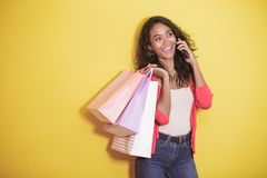 Asian woman with shopping bag talking on a mobile phone. Portrait of asian woman with shopping bag talking on a mobile phone on yellow background Stock Image