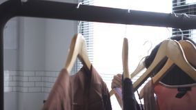 Asian woman shopping clothes. Shopper looking at clothing on the rail indoors in clothing store. Beautiful happy smiling asian woman model. Medium shot stock video