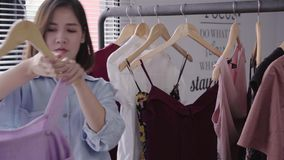 Asian woman shopping clothes. Shopper looking at clothing on the rail indoors in clothing store. Beautiful happy smiling asian woman model. Medium shot stock video footage
