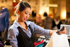 Asian Woman in shopping mall. Woman of Asian - Chinese - origin in a shopping mall downtown looking for clothes stock photo