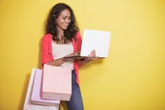 Asian woman shopping at online shop using laptop. Portrait of asian woman shopping at online shop using laptop on yellow background Stock Photography