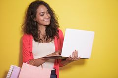 Asian woman shopping at online shop using laptop. Portrait of asian woman shopping at online shop using laptop on yellow background Stock Image