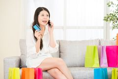 Asian woman shopping online with smartphone credit card. Charming asian woman shopping  online with smartphone pay by credit card sitting on sofa colorful Royalty Free Stock Photos