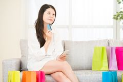 Asian woman shopping online with smartphone credit card. Charming asian woman shopping  online with smartphone pay by credit card sitting on sofa colorful Stock Photos