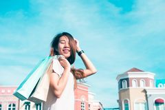 Asian woman shopping an outdoor flea market with a background of pastel buildings. Close up of a young Asian woman shopping an outdoor flea market with a Royalty Free Stock Photos