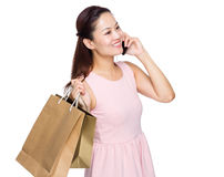 Asian woman shopping and talking on mobile phone Royalty Free Stock Photo