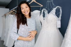 Asian woman shopping for wedding dress stock photography