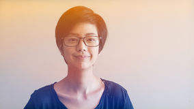 Asian woman  with short hair and glasses on color background Stock Photography