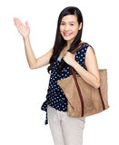 Asian woman with shoulder bag and hand present something Stock Images