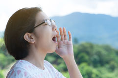 Asian woman shouting. Happiness of Young Asian woman shout and scream using her hands on mountains landscape background. copy space Stock Photography